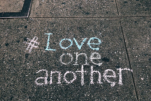 """Pavement with chalk writing """"Love one another"""""""