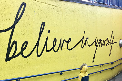 "text on yellow wall ""Believe in yourself"""