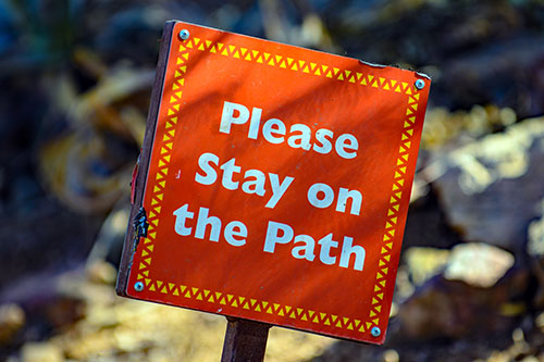 "text on red paper ""please stay on the path"""